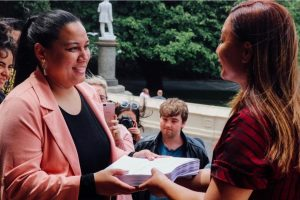 """Melissa Lama presenting the Petition against """"Armed Response Trials"""" at Parliament steps to Green Party co-leader Rt. Hon. Marama Davidson."""