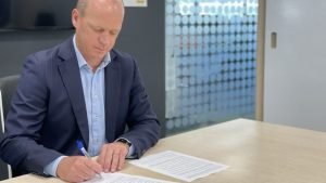 Chris James is signing the gazette notice to grant provisional approval for New Zealand's use of the Pfizer and BioNTech COVID-19 vaccine Comirnaty - Ministry of Health image